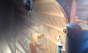 Grit blasting the de-barker drum prior to application of abrasion resistant lining.
